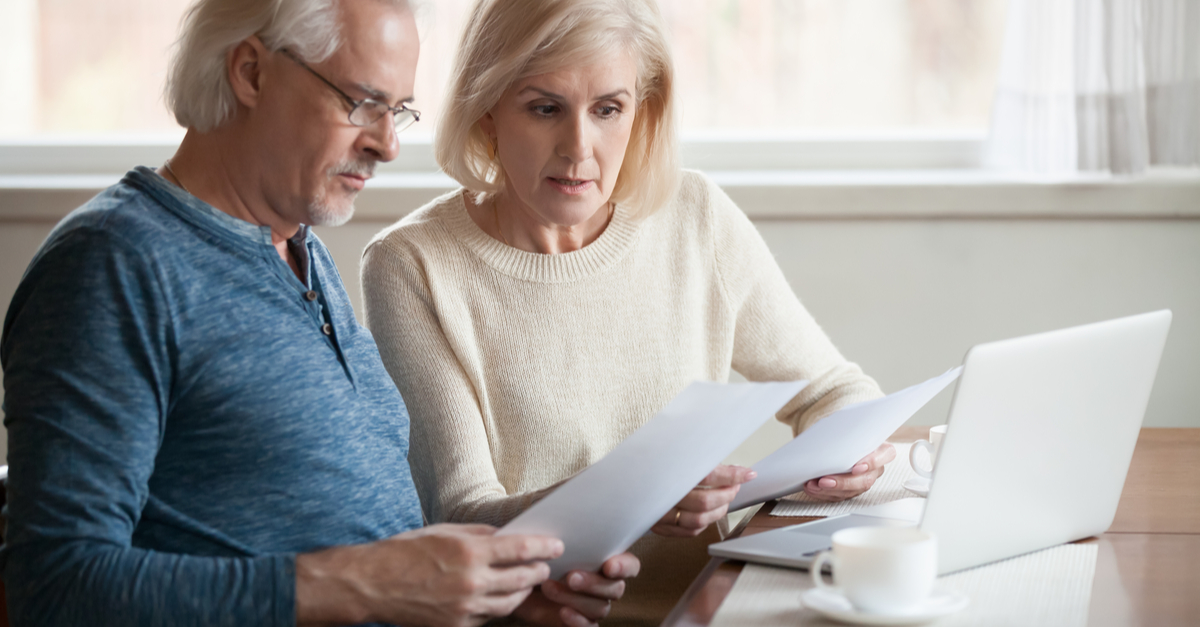 A worried couple looking at a mortgage payment document