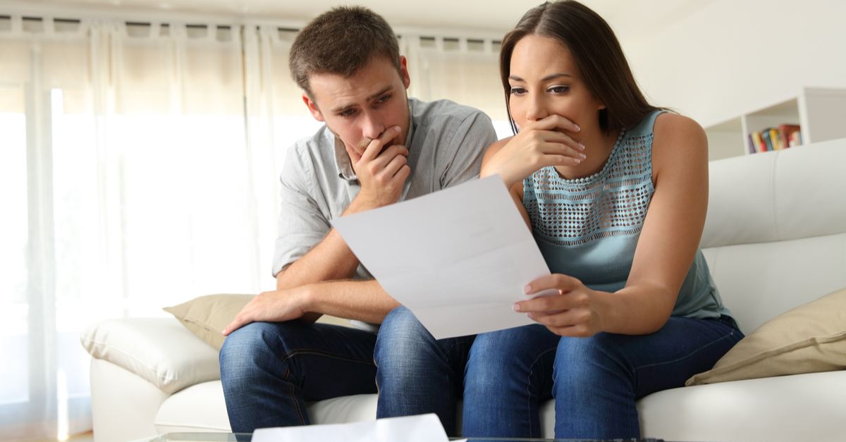 worried couple reading a foreclosure notice