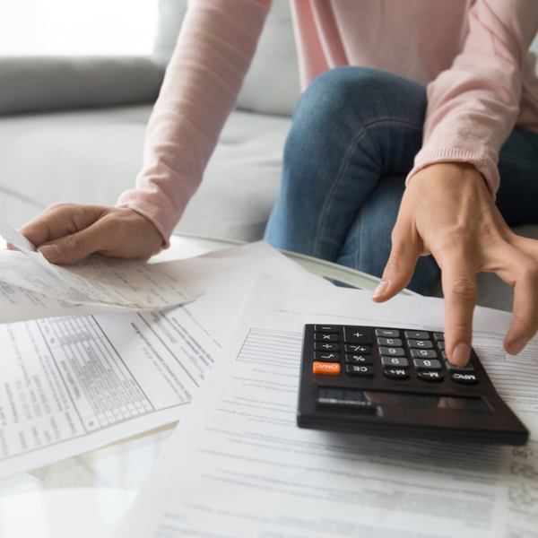 Woman holding paper bills using calculator